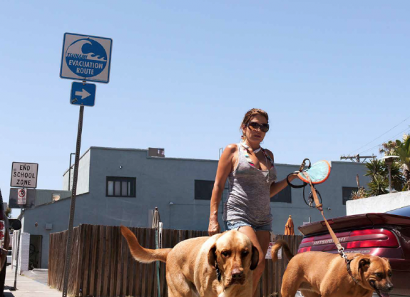 Monica Nouwens, June 2014, Venice, California; A young woman walks her dog in Venice, CA., below a Tsunami Evacuation Zone sign.