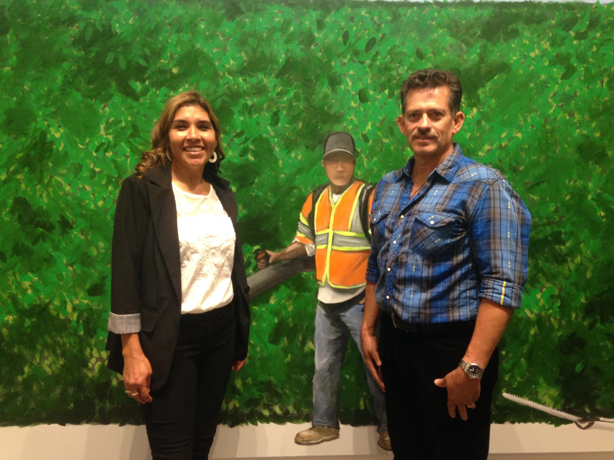 "Maria Gomez and Ramiro Gomez Sr. at the opening of ""On Melrose"" at Charlie James Gallery on April 16, 2016. They are standing in front of their son's painting ""Paramount Studios,"" 2016."