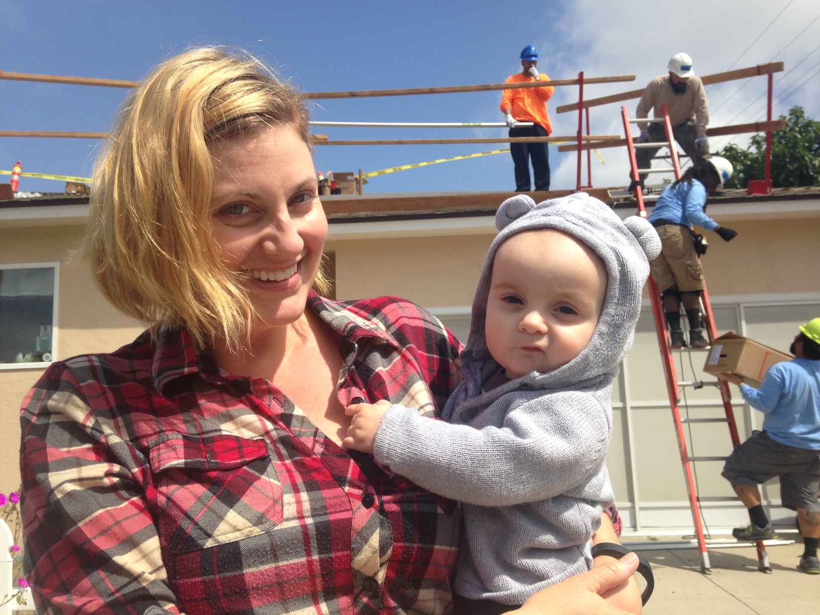 Amanda Penny and her son Max in front of their Long Beach home, where GRID Alternatives volunteers are installing a solar panel. Photos by Avishay Artsy.