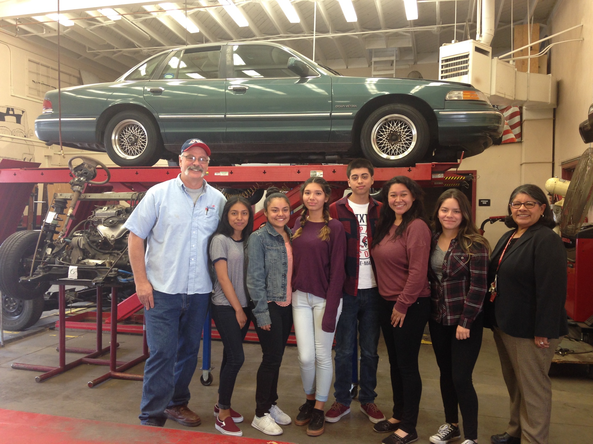 Joseph Agruso has been teaching automotive classes at Van Nuys High School for a dozen years. Here he poses with several of his students.