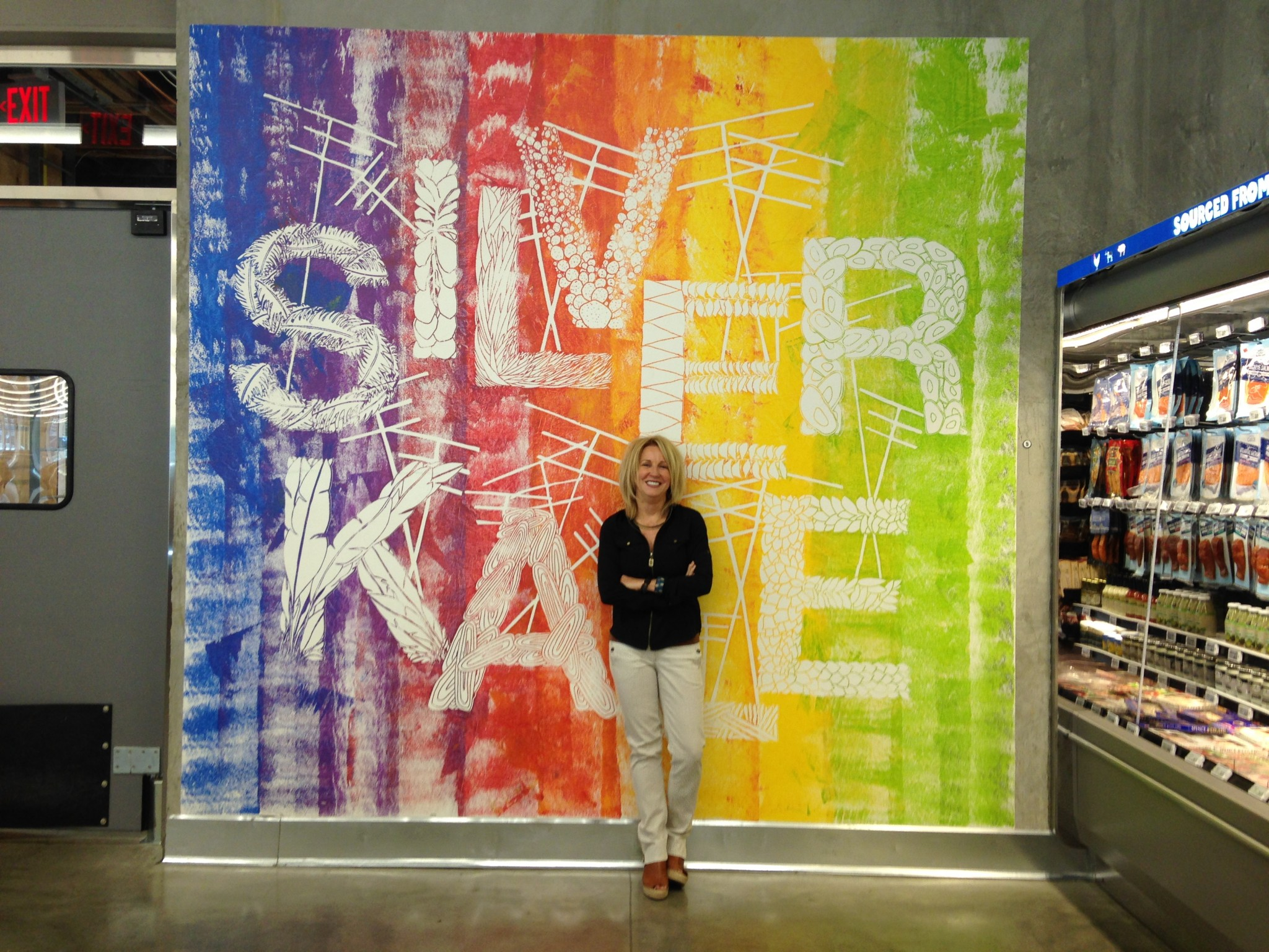 Deborah English poses in front of her Silver Kale mural at the 365 by Whole Foods Market. Photo by Avishay Artsy.