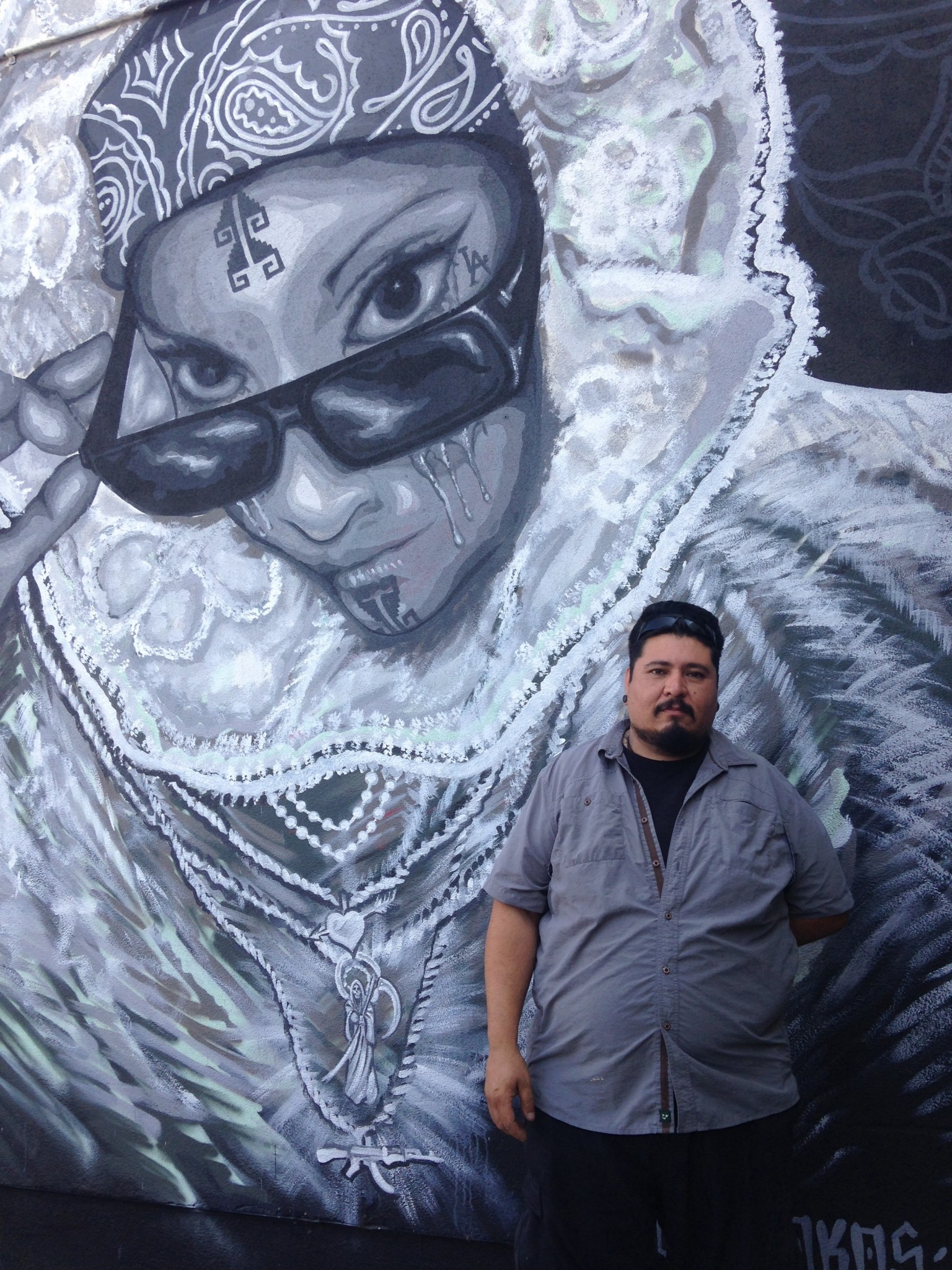 Raul Gonzalez, an artist and Boyle Heights native who was priced out of his nearby studio after his rent tripled, poses in front of a mural outside of Self Help Graphics & Art. Photo by Avishay Artsy.