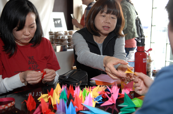 Teachers and participants fold origami cranes at Angeli Caffe. Organizer Samin Nostrat's goal was a thousand cranes, which symbolize good fortune and peace.