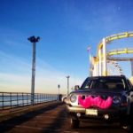 A pink-mustached Lyft car at the Santa Monica pier on Lyft's Facebook page.