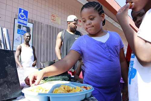 Children in South LA taste fresh fruit at the farmer's market. (Photo by Shako Liu)