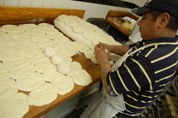 "Sybil's roti prep man ­ nicknamed ""Number One"" ­ works hundreds of balls of dough into flat, raw patties ready to be baked."