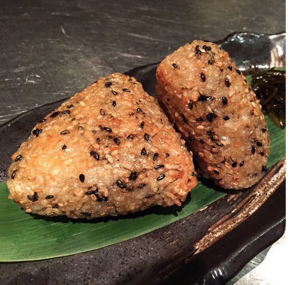 The Yaki Onigiri or grilled rice ball is sprinkled with sesame seeds and Shiso, and splashed with soy sauce. Each rice ball is hand-made and slow-grilled to order.
