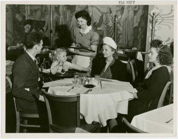 """Restaurants - Childs - Childs waitress serving food to family: Celela Bonner, Child's waitress, serving Chattanooga, Tennessee family: (left to right) Mr. R.F. Lowe, Carolyn Joyce Lowe (3 years old), Mrs. Lowe, and Betty Fritz Lowe."" New York Public Library Digital Collections. Accessed January 15, 2016. http://digitalcollections.nypl.org/items/5e66b3e8-c98c-d471-e040-e00a180654d7"