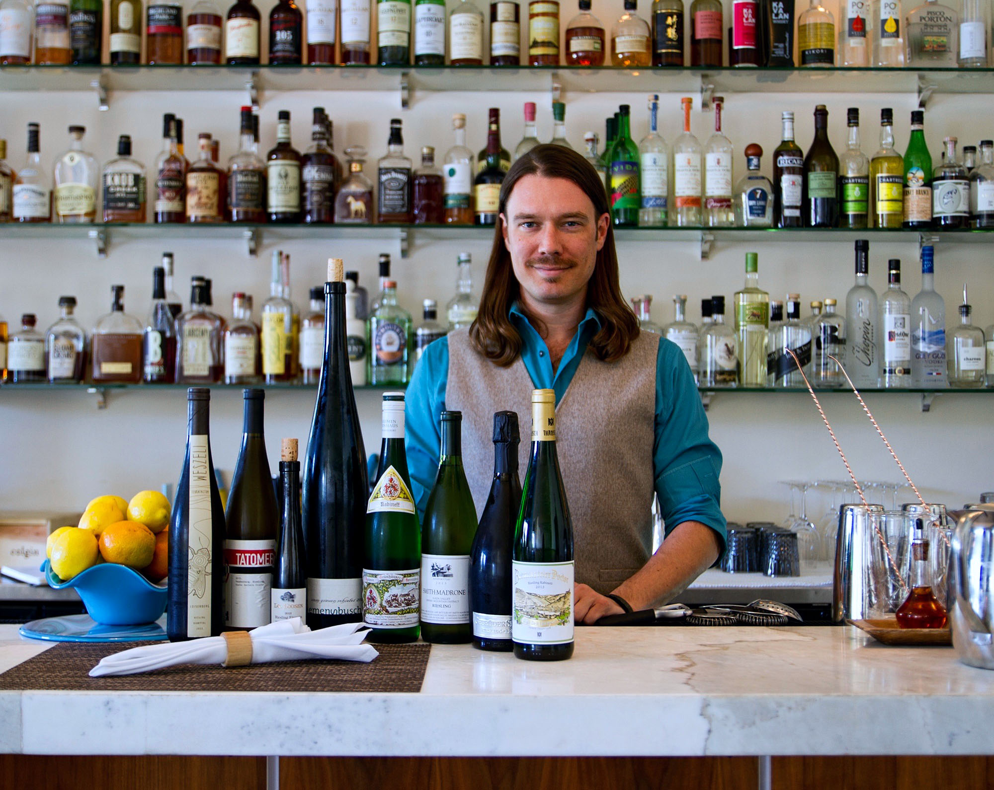 Co-owner and wine director Drew Langley displays his summer Riesling collection. (Photo by Camellia Tse/KCRW)