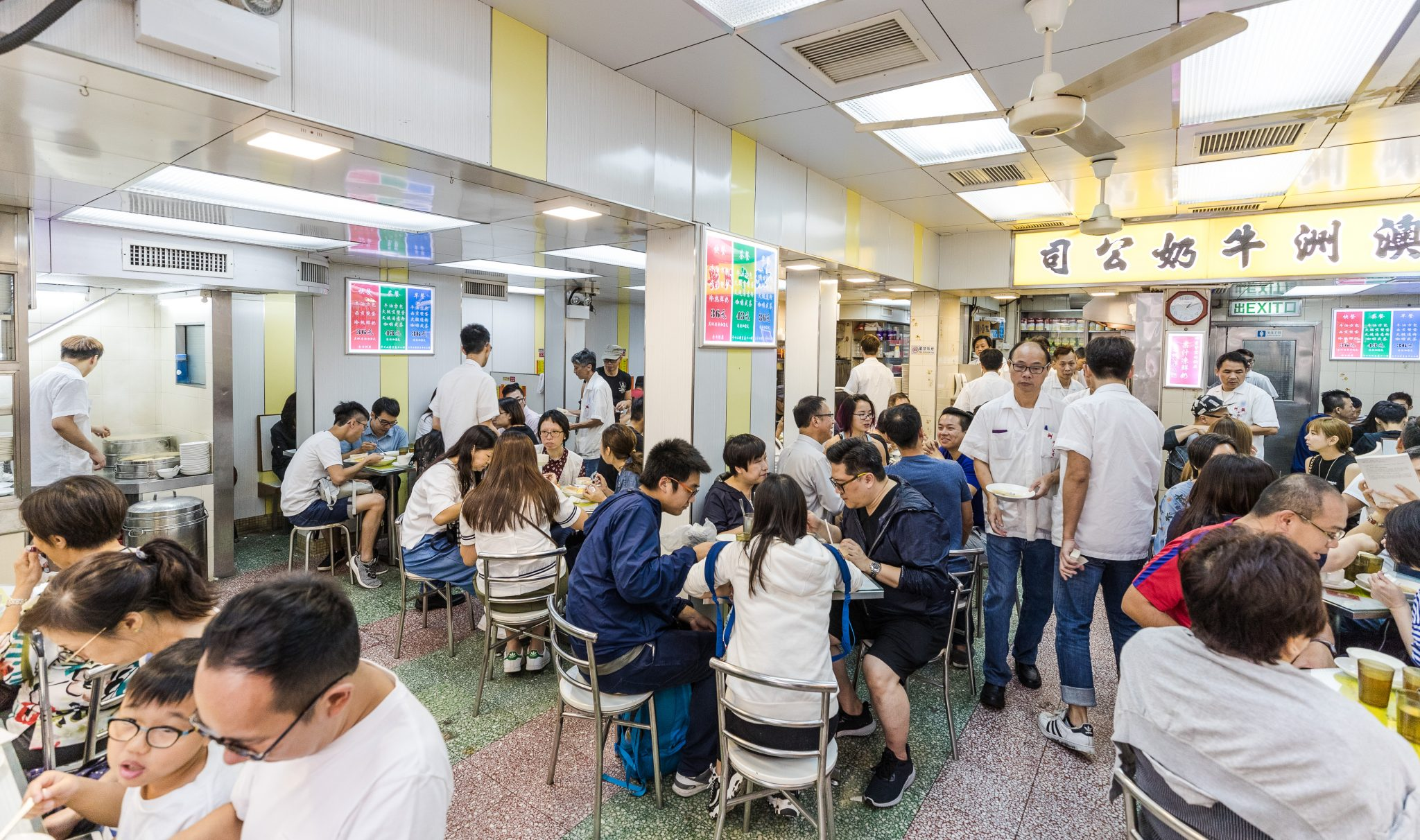 The dining room of Australia Dairy Company, where customers squeeze into small booths and around tables for soup, egg sandwiches and steamed milk pudding. Photo by Stan Lee