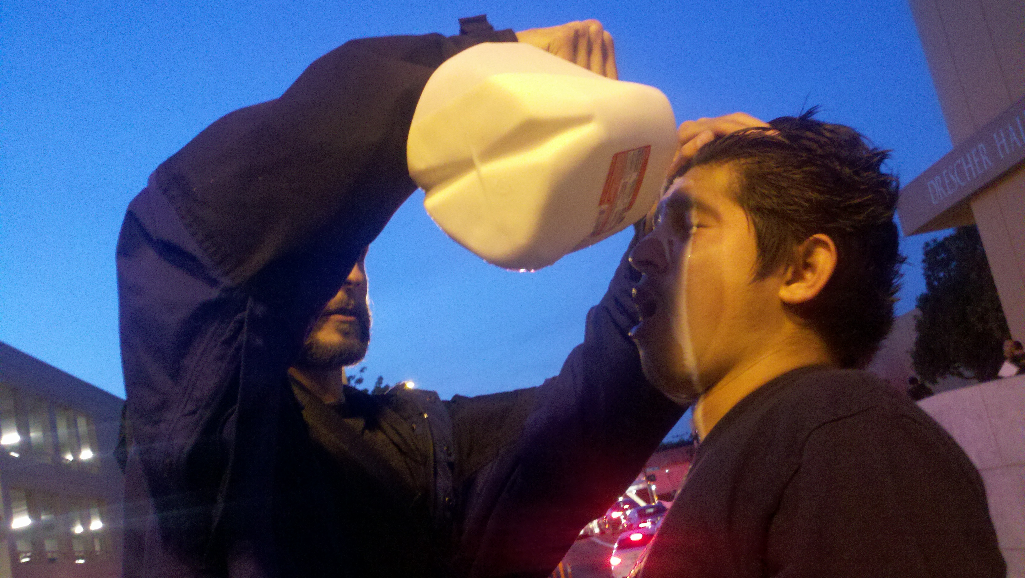 April 3, 2012. A student pours milk in the eyes of a co-protester who was sprayed by pepper spray.