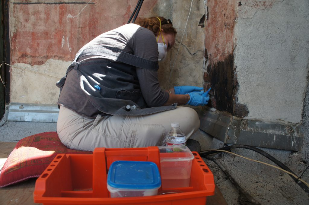 Much of the conservation work invovles cleaning tar residue that splattered on the mural from roofing projects