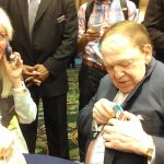 Sheldon Adelson at the Republican Jewish Coalition event, putting on a button that says &quot;Obama... Oy Vey&quot;