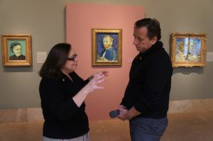 With the artist looking on in his self-portrait, Norton Simon curator Carol Togneri shares her knowledge and affection for Vincent Van Gogh with KCRW's Saul Gonzalez. The painting is flanked by some of Van Gogh's other works, including a portrait of his mother to the left.