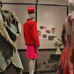Vitrines display costumes from LACMA's permanent collection. From left to right: 2002/03 denim jacked by Comme des Garcons, a two-piece suit from 1988 by Yves Saint Laurent, and c.1972 evening dress by Geoffrey Beene. These were selected by the artist as sources of inspiration.