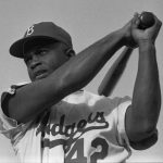 No. 42, Jackie Robinson swinging a bat in Dodgers uniform, 1954.