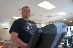 "Most mornings, Sgt. Craig can be found in Casa Colina's gymnasium, walking the treadmill.  Shot in 2010 in Afghanistan and having undergone seven surgeries, he still has fragments of the bullet in his head. ""I'm a medical miracle,"" he says with mordant humor. (Photo by Saul Gonzalez)"
