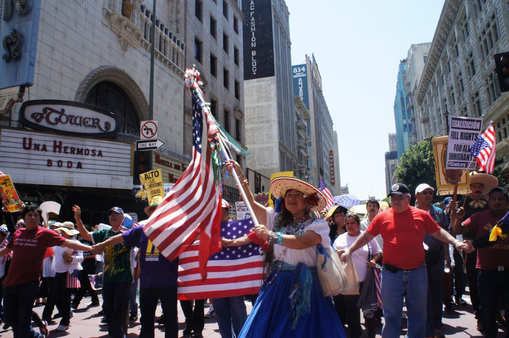 There was a big dash of street theater in the march, from dancers dressed up as Aztec warriors to Asian drumming groups to this woman wearing 19th Century fashion and carrying both a U.S. and Mexican flag.