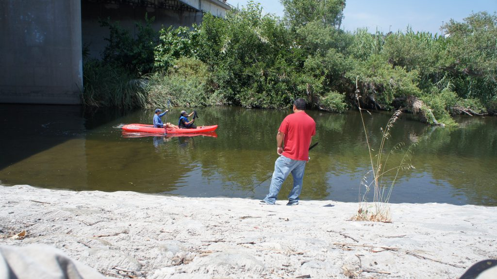 Those who paddle this stretch of the L.A. River will share the waterway with a small group of people who regularly fish from its banks. Fishing from boats is also allowed.  (Photo by Saul Gonzalez)