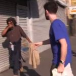 Greg Karber tries to hand a homeless man on Skid Row clothes from Abercrombie &amp; Fitch.