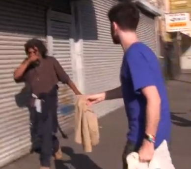 Greg Karber tries to hand a homeless man on Skid Row clothes from Abercrombie & Fitch.