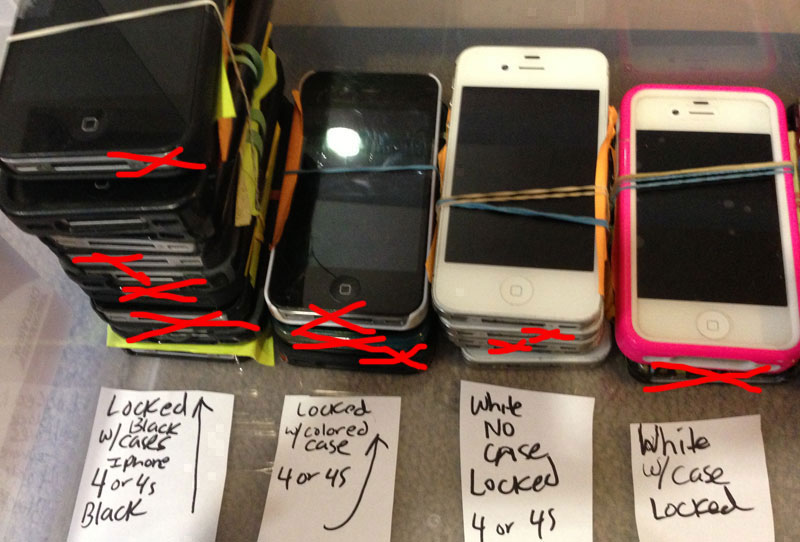 "A stack of lost phones. The red ""x"" denotes a phone that's been claimed."