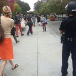 Police officer escorts KCRW staff during Friday's lockdown.