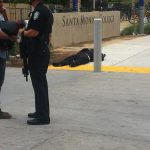 A police officer guards the body of the alleged gunman at the Pearl Street entrance to Santa Monica College