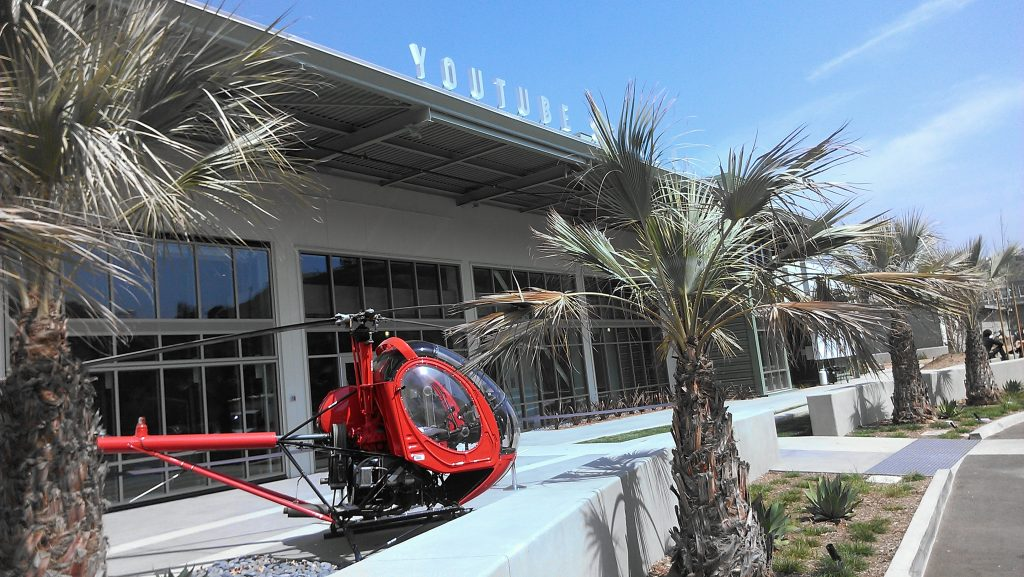 A red Hughes 269A helicopter sits in front of YouTube Space LA, once an aircraft hangar owned by Howard Hughes.