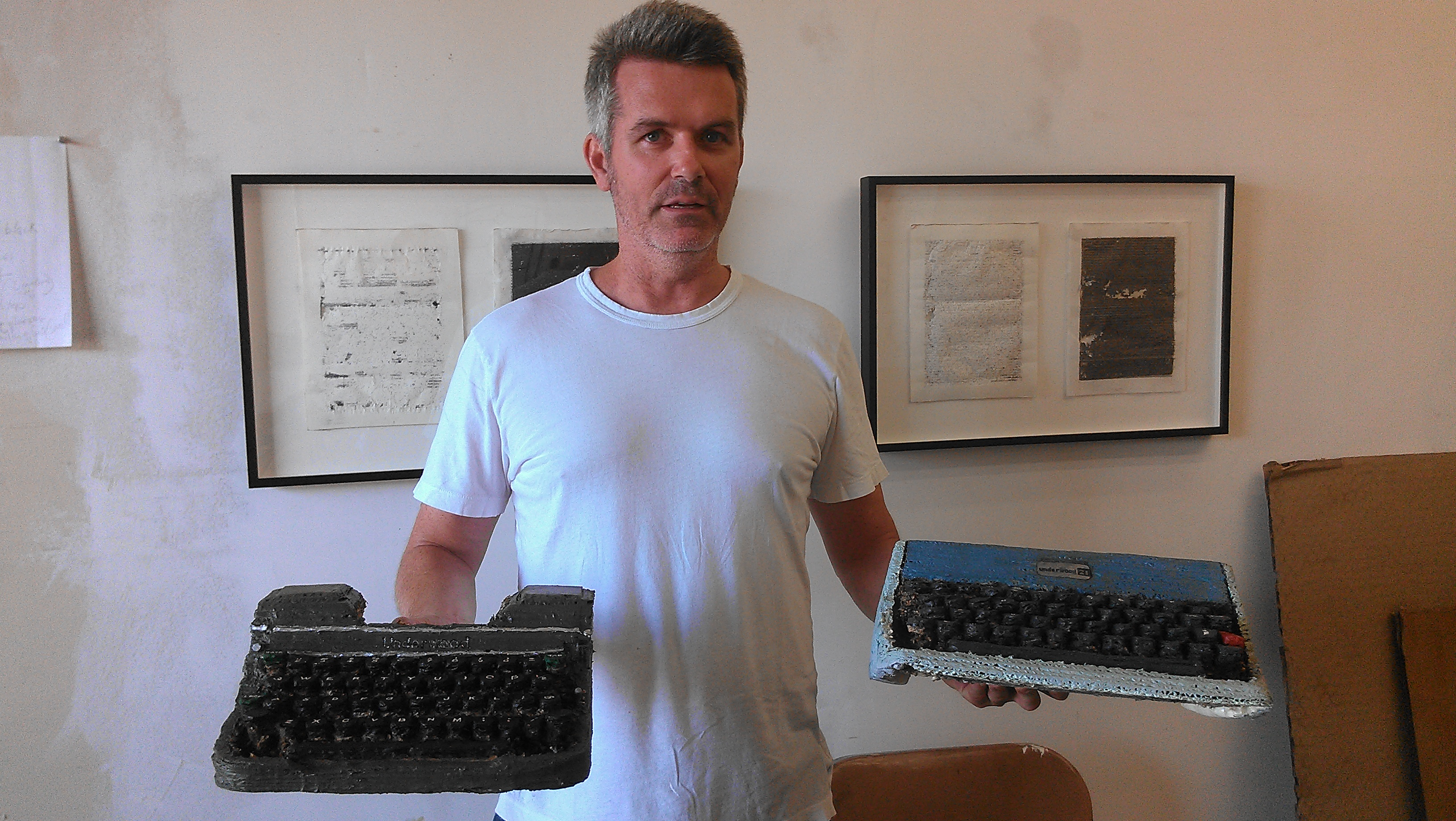 Tim Youd holds two of his cardboard replica typewriters.