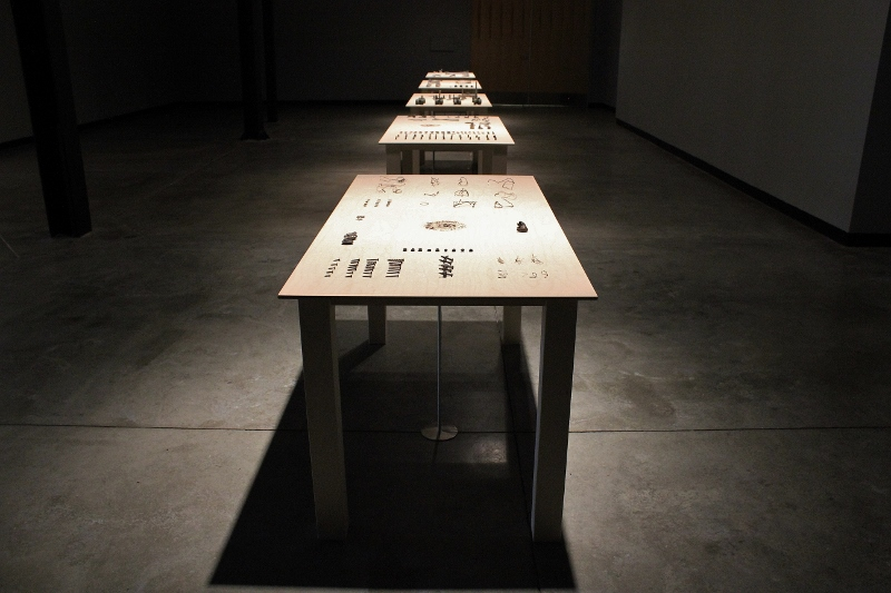 A view of Adriana Salazar's installation at the Grand Central Art Center in Santa Ana. The installation consists of five wooden tables displaying used medical implants that the artist retrieved from crematoriums Credit: Carolina A. Miranda