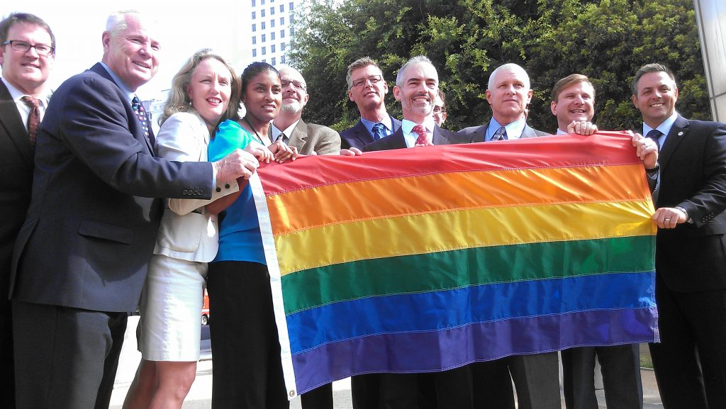 City council members and gay rights advocates hold a rainbow gay pride flag near the Sister Cities marker in downtown LA.