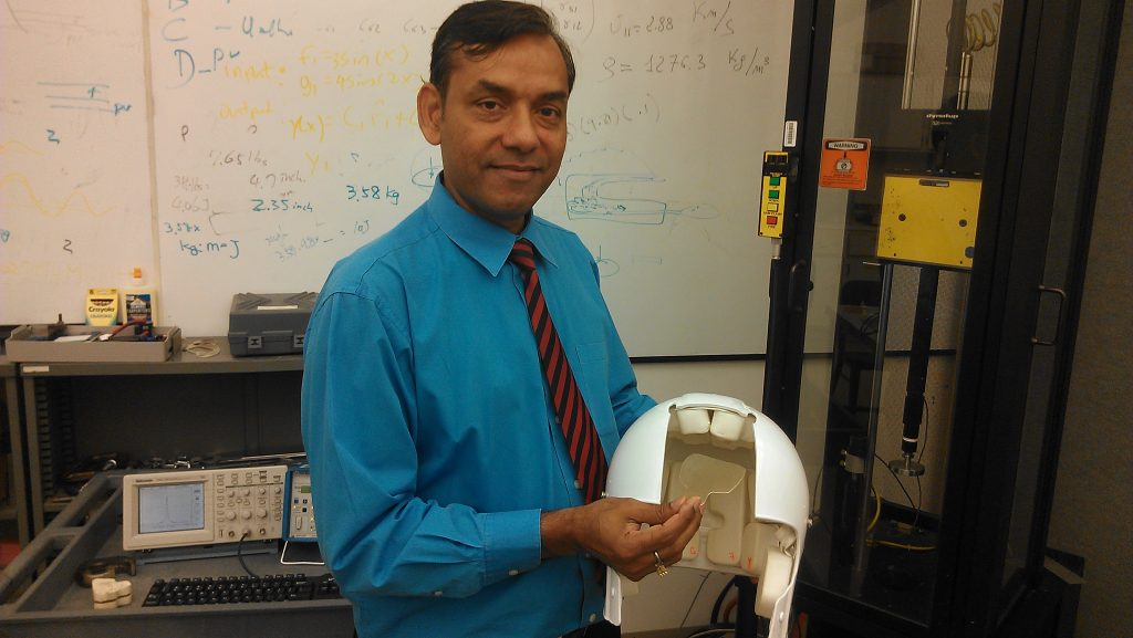 UCLA engineering professor Vijay Gupta and the football helmet and polymer material used in his experiments. Photo by Avishay Artsy.