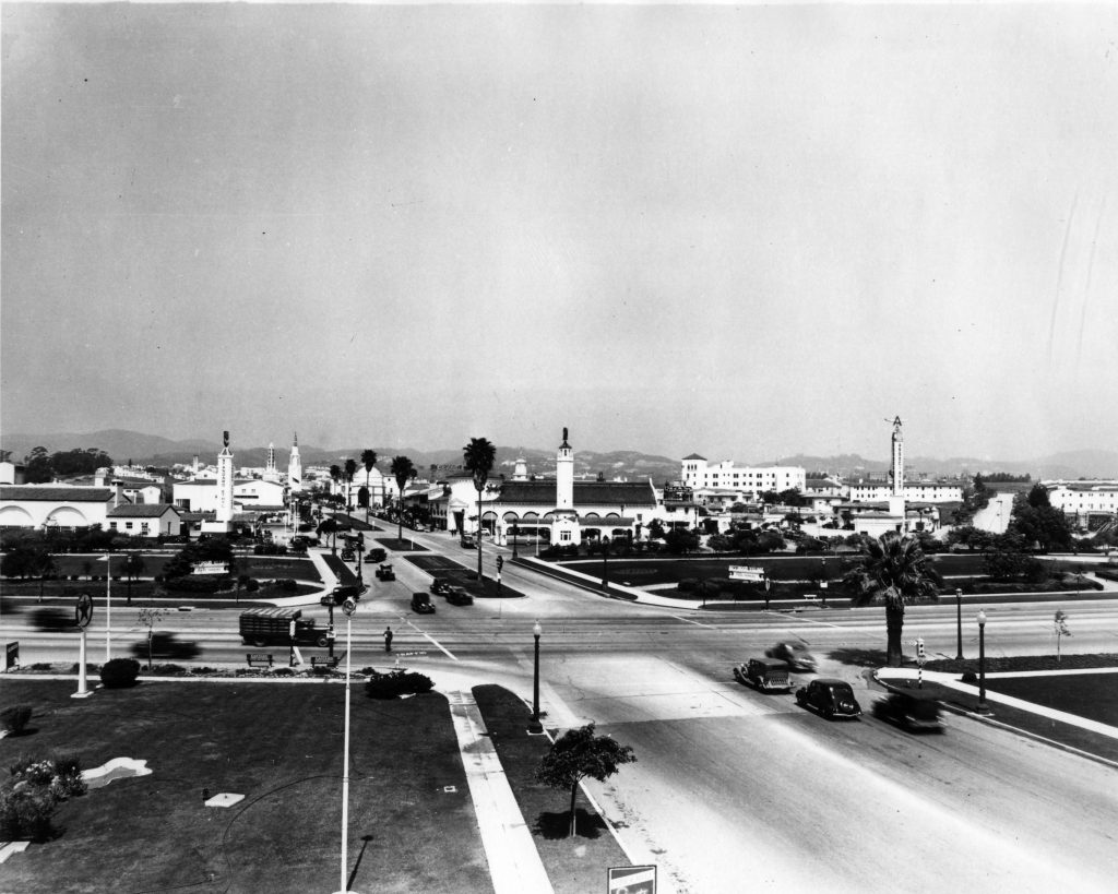 "7.WILSHIRE & WESTWOOD, 1939:  Looking north on Westwood Boulevard at Wilshire, one can see the many towers that served as Village landmarks, including the Fox Theater Tower, Sears Roebuck & Co. Tower, Holmby Hall Clock Tower, and four gas station towers that lined Lindbrook Drive.  The towers served to orient pedestrians within the Village, and were intended to catch the eye of motorists as they sped along in the ""fast moving traffic"" along Wilshire Boulevard.  Note the absence of any traffic signals at this busy intersection!  Photo and caption courtesy of Steven Sann."