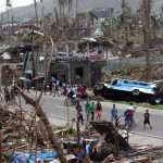 On 9 November, residents walk past downed trees and destroyed homes and cars, on a road in Tacloban City – one of the areas worst affected by Super Typhoon Haiyan – on the central island of Leyte.  (Photo by Jeoffrey Maitem/ UNICEF)