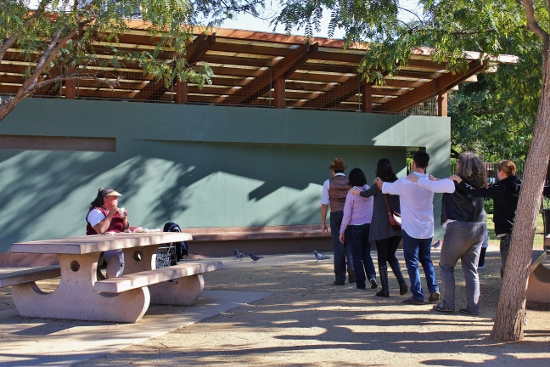 The group tries to find their way around a structure in the park as a visitor looks on.