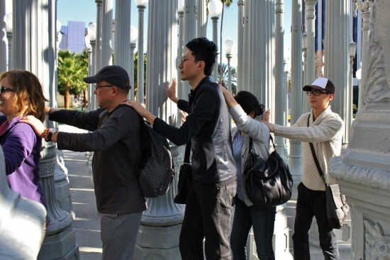 "The artist ended the tour by weaving repeatedly through Chris Burden's lamp post installation ""Urban Light"" at LACMA. A group of tourists closed their eyes and joined the end of the line."
