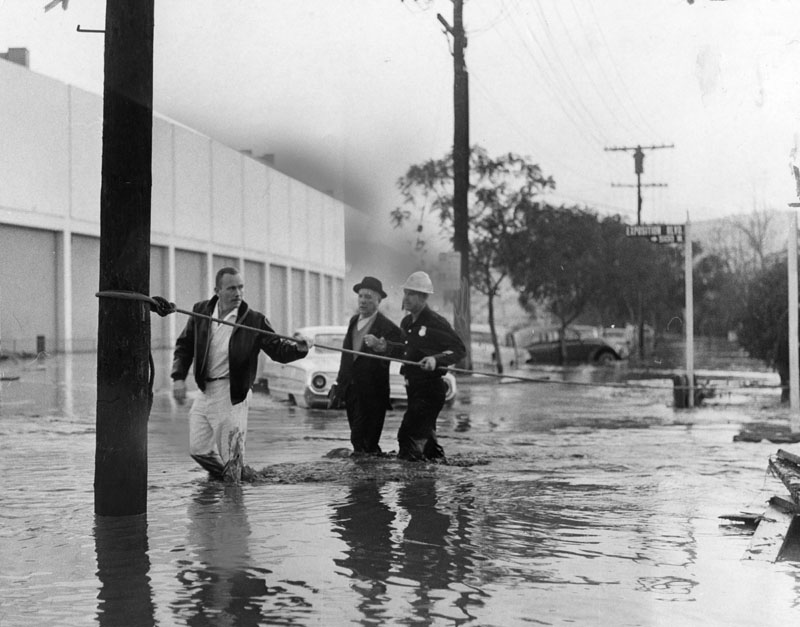 Firemen escort flood victims in Baldwin Hills in the aftermath of the Baldwin Hills Dam disaster. They wade through the street using a safety rope. Photo dated: Dec. 15, 1963.  Photography by Joe Rustan, courtesy: Los Angeles Public Library