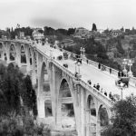 View of the Colorado Street Bridge shows several groups of people walking on the bridge and enjoying the surrounding scenery. A few automobiles can be seen travelling on the bridge. Photo courtesy: Los Angeles Public Library