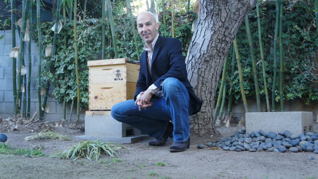"Paul Hekimian, also with HoneyLove, is a second-generation beekeeper in Santa Monica. Beekeeping, unlike some other urban areas,  isn't explicitly legal in Los Angeles.  Hekimian and other members of HoneyLove are lobbying to change that. He'd like to see L.A. adopt rules similar to what Santa Monica has in place. ""The ordinance here in Santa Monica is very simple,"" says Hekimian. You are allowed to have two hives facing five feet away from your neighbor's property line.""  (Photo by Saul Gonzalez)"