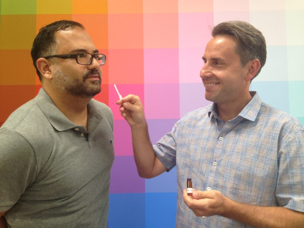 KCRW's Steve Chiotakis, left, takes a big whiff of East LA from a scent strip held by artist Brian Goeltzenleuchter.
