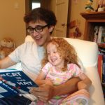 Jason Boog reads with his daughter, Olive.