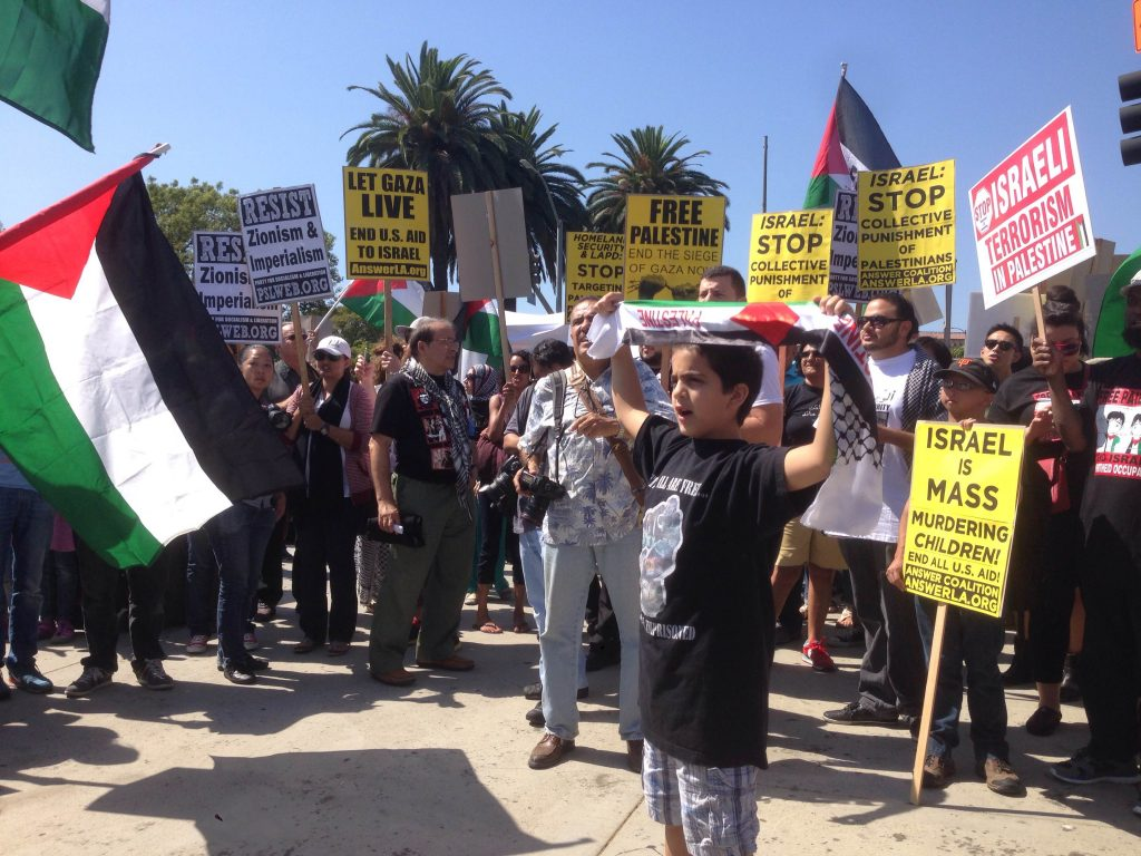 People hold signs at an anti-Israel protest on July 20, 2014. (Photo: Benjamin Gottlieb)