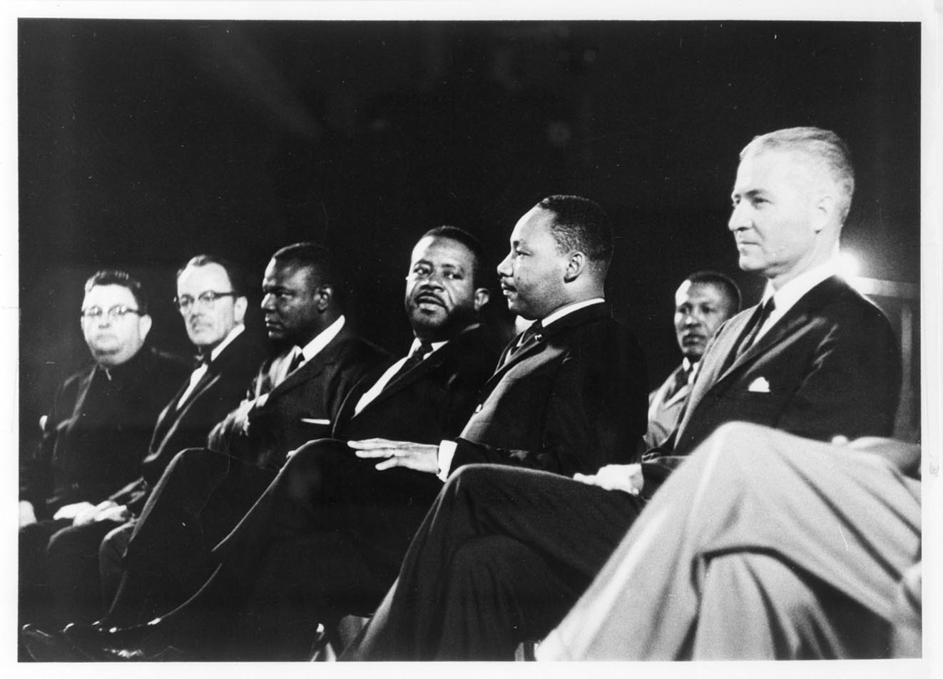 "From right to left: G. Homer Durham, Martin Luther King, Jr., Ralph Abernathy, an unidentified participant, Rev. Louis Eaton and Msgr. Robert Donahoe at Goodwin Stadium, Arizona State University. Martin Luther King addressed an audience of 8,000 people on the topic ""Religious Witness for Human Dignity."" June 3, 1964 Photo by: MRD #2, Monsignor Robert Donahoe Collection, Arizona Collection, Arizona State University Libraries"