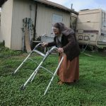Sister Jean Marie walks through freshly sprouted clover around the mobile homes that she lives in with Sister Patricia and Sister Mary Anne. This is where they've resided since the monastery project went belly up. Photo by Paul Wellman