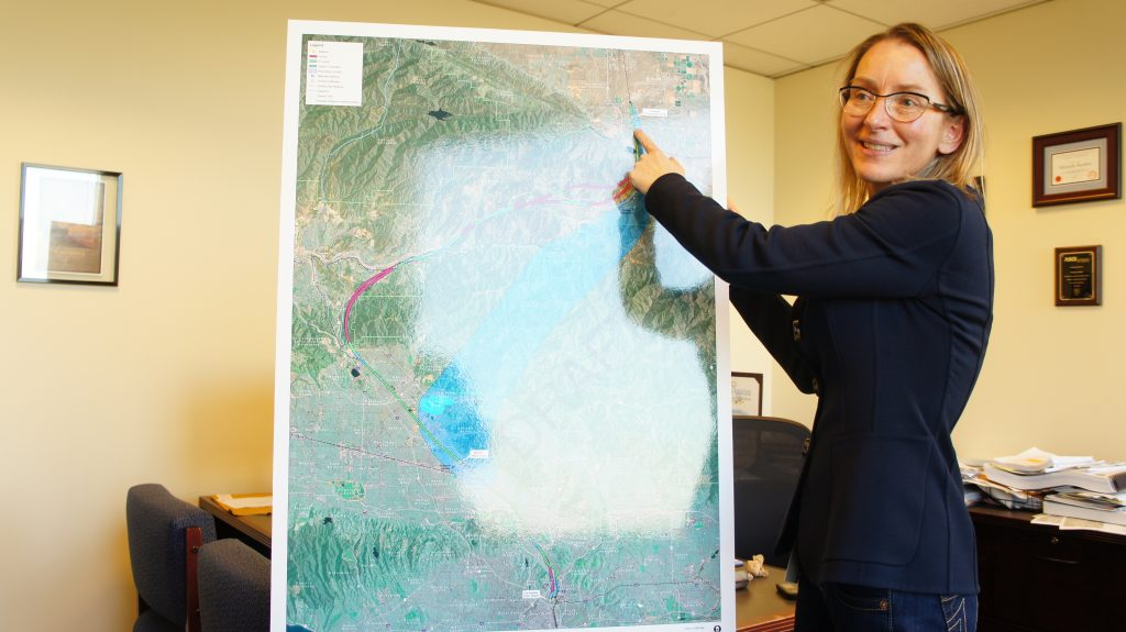 """Michelle Boehm, seen here with a map of potential train routes, is the Southern California Regional Director for  the California High Speed Rail Authority. She says her agency is doing everything possible to select routes that are sensitive to local concerns. """" It's just hard. It's just really hard,"""" says Boehm.  And honestly I  understand how hard it is when the conversation is about your home, about the street that your children walk down to get to school. And about your community. And there is nothing that can change the fact that it is hard."""" Boehm also asks residents to remember the long-term benefits that the train is supposed to bring, from thousands of construction jobs to reduced commute times once the train is built and train starts running. (Photo: Saul Gonzalez)"""