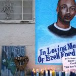 Candles burn at a memorial for Ezell Ford in Los Angeles as protestors demonstrate as people gather to protest after two grand juries decided not to indict the police officers involved in the deaths of Michael Brown in Ferguson, Mo. and Eric Garner in New York, N.Y. on December 05, 2014 in Los Angeles, United States. (Photo by Mintana Neslihan Eroglu/Anadolu Agency/Getty Images) | Anadolu Agency via Getty Images