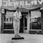 Man sweeps broken glass in front of Chesley Jewelry store, in Watts. Photo Courtesy: Los Angeles Public Library
