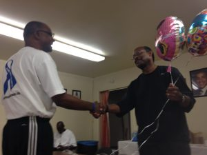 Freddie Muse, left, offers cancer survivor James Tinsley balloons and cupcakes in honor of his wife's birthday. Photo by Avishay Artsy